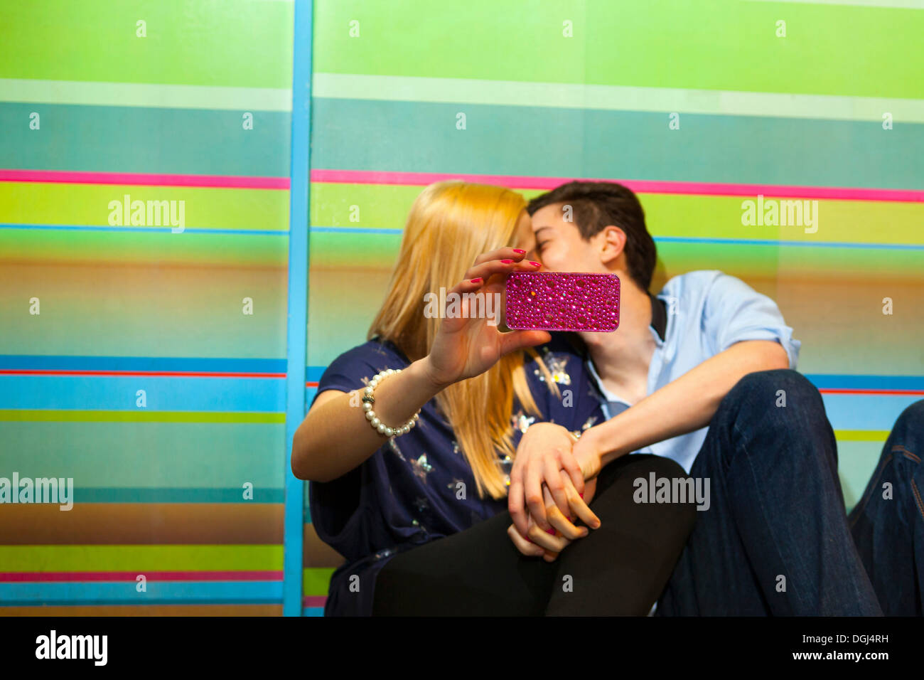 Young couple taking self portrait photograph of kiss - Stock Image