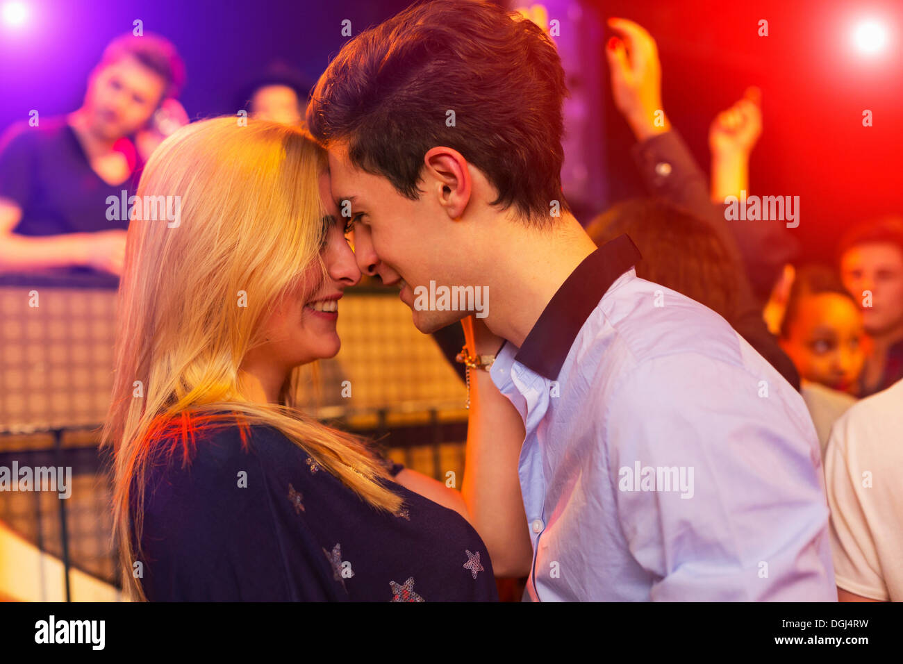 Young couple face to face at party, group behind - Stock Image
