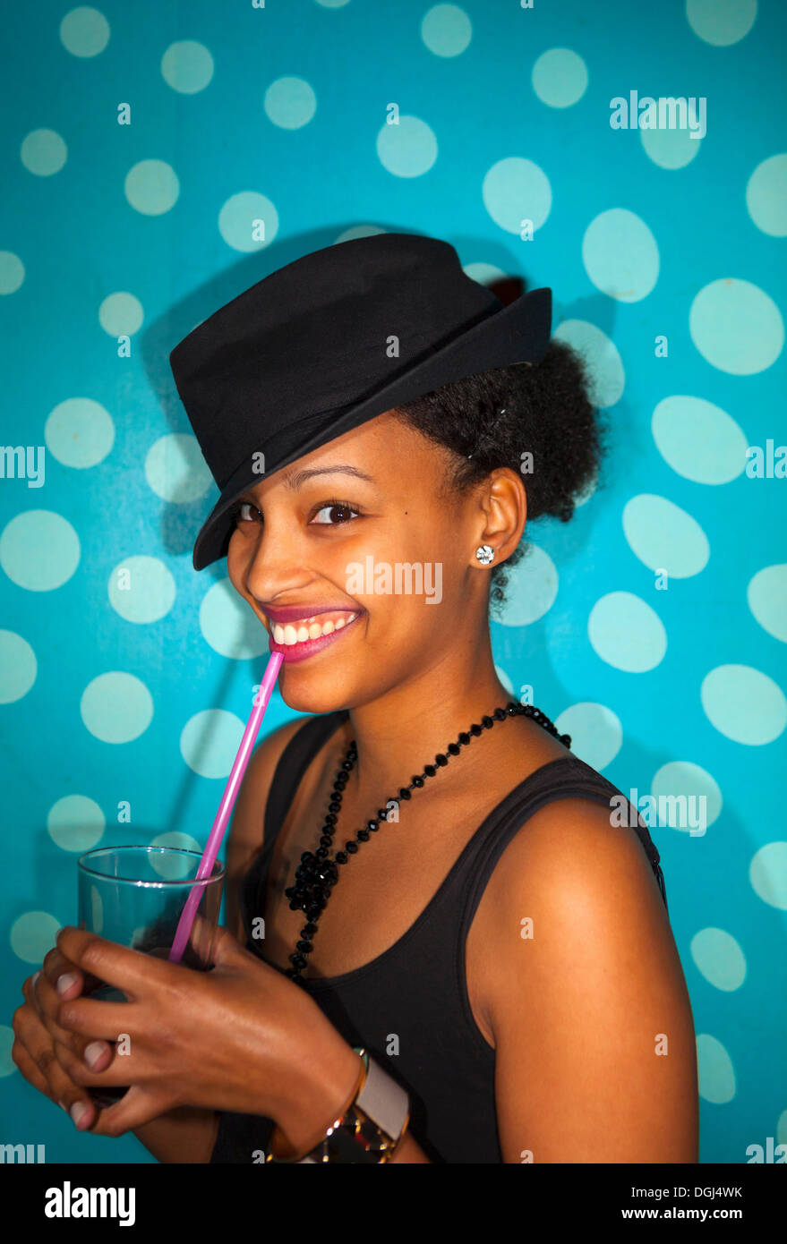 Portrait of young adult woman with mixed race ethnicity smiling and holding drinking glass with straw - Stock Image