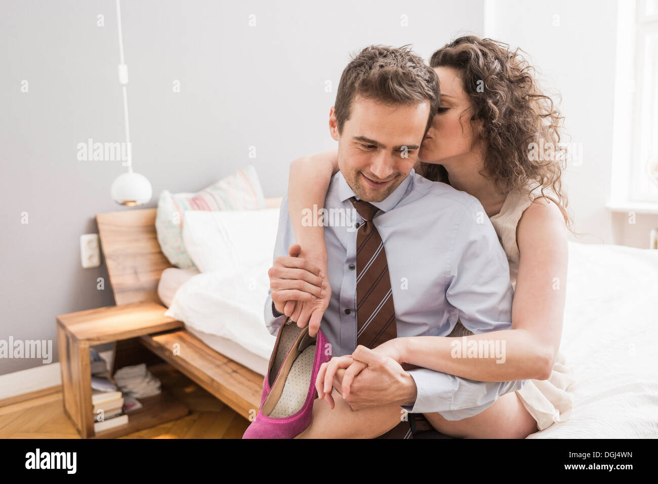 Mid adult couple face to face with arm around, smiling and holding shoe - Stock Image