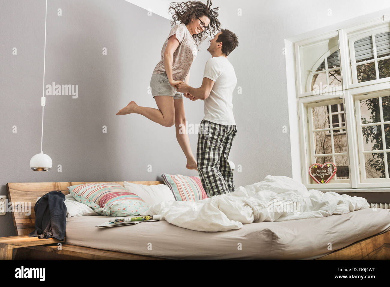 Mid adult couple wearing pyjamas jumping on bed - Stock Image