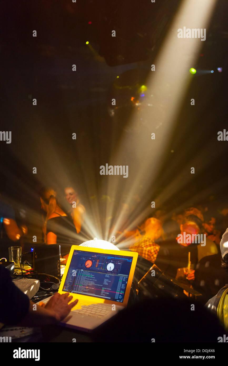 Nightclub scene with people dancing, disc jockey mixing desk with computer - Stock Image