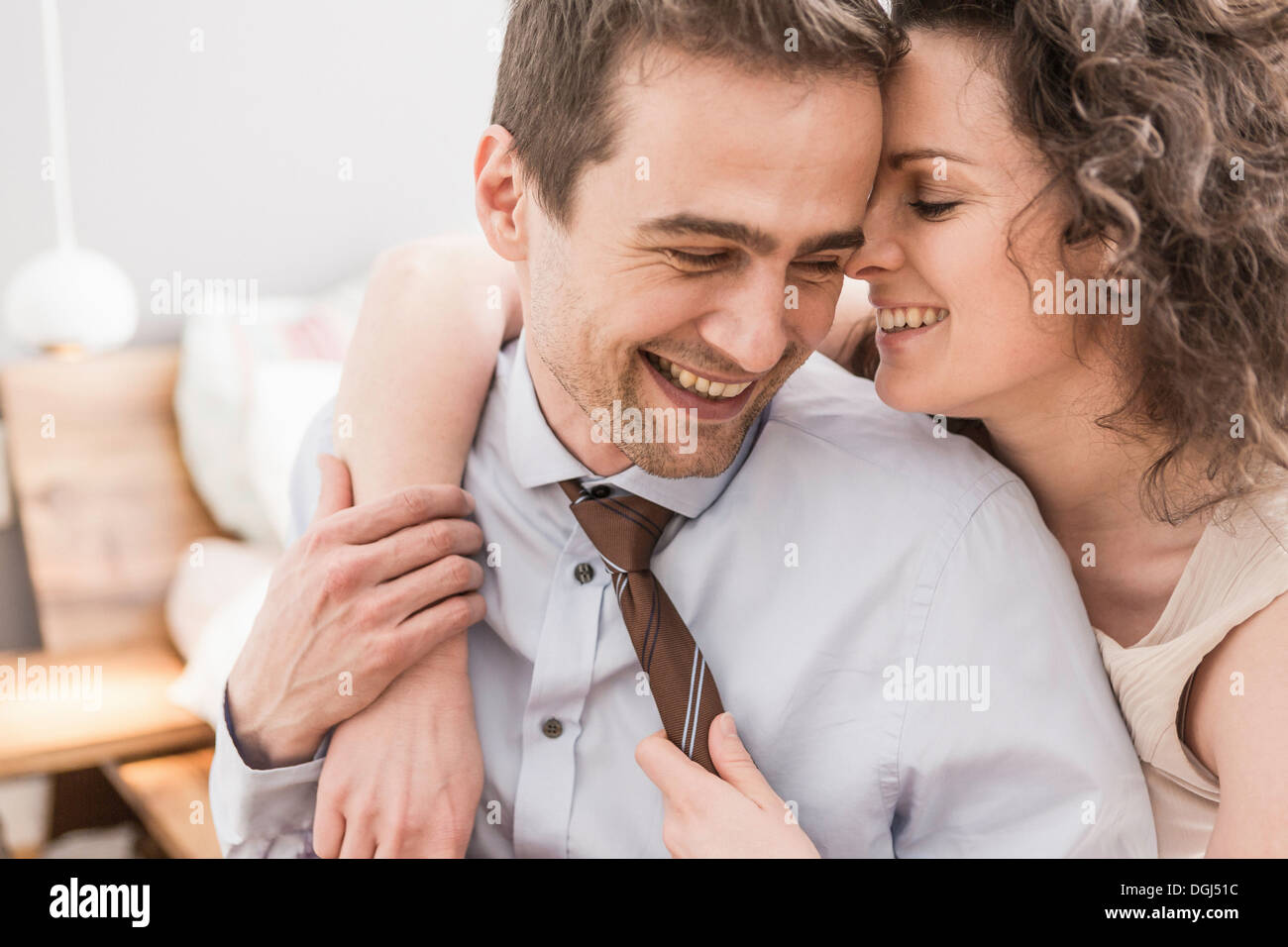 Mid adult couple face to face with arm around, smiling - Stock Image