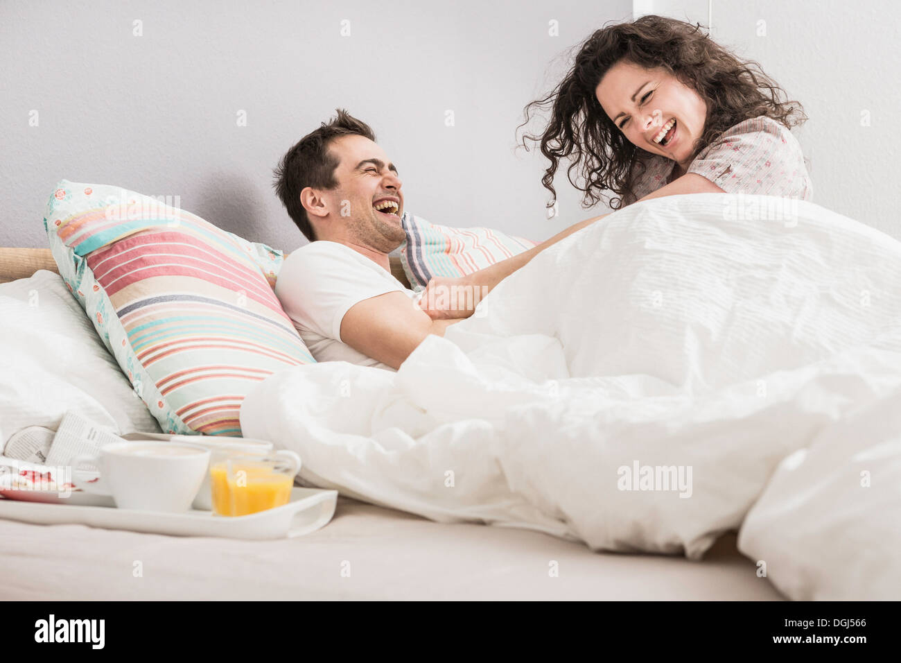 Mid adult couple lying in bed, breakfast on tray, pillow fight - Stock Image