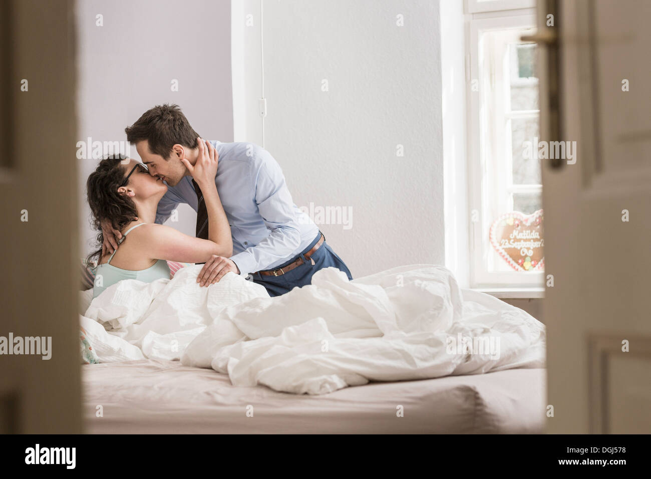 Mid adult couple kissing on bed - Stock Image