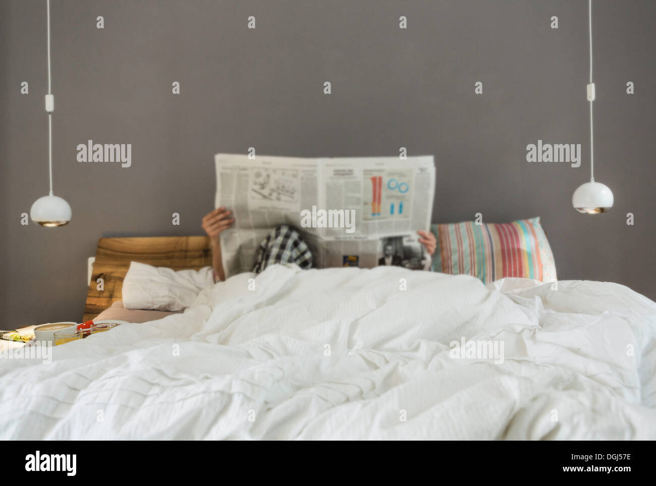 Mid adult couple reading newspaper in bed, faces obscured - Stock Image