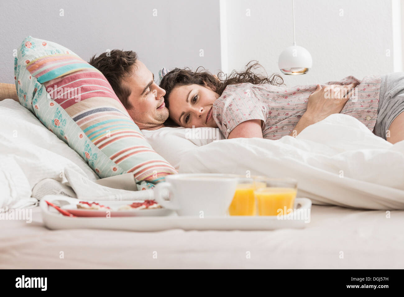 Mid adult couple lying in bed, breakfast on tray, hugging - Stock Image