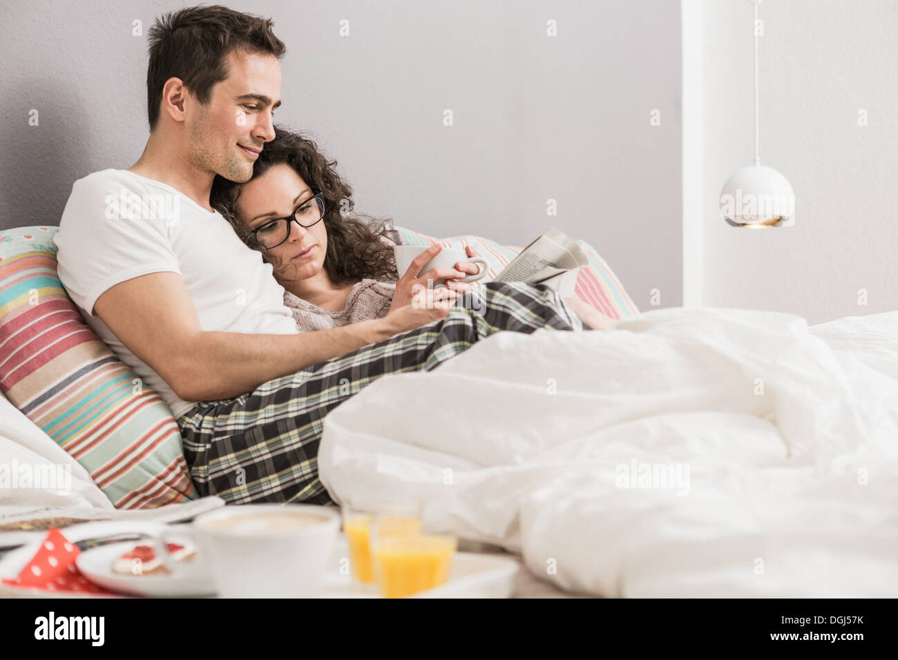 Mid adult couple reading newspaper in bed - Stock Image