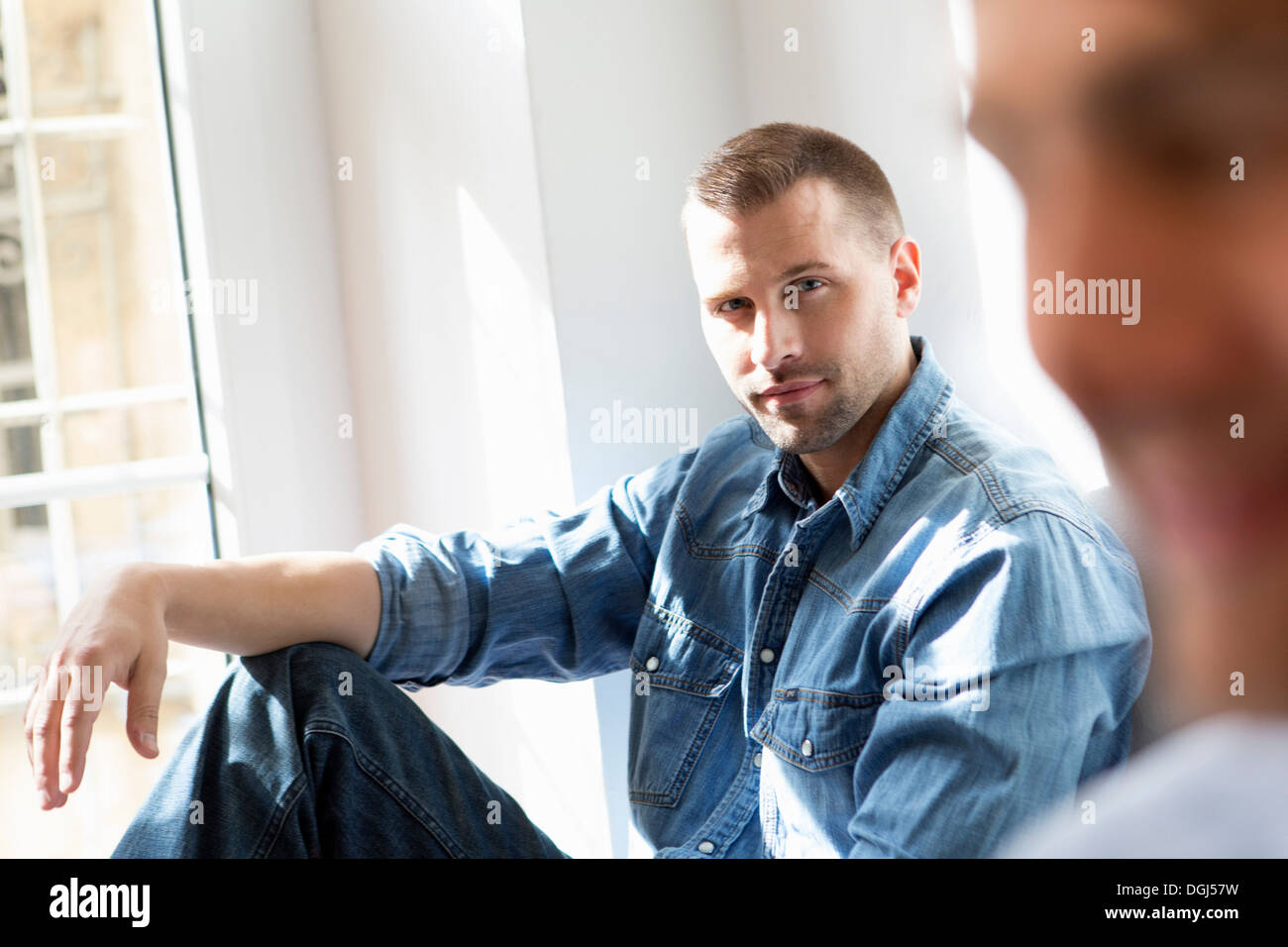 Mid adult man wearing denim shirt - Stock Image