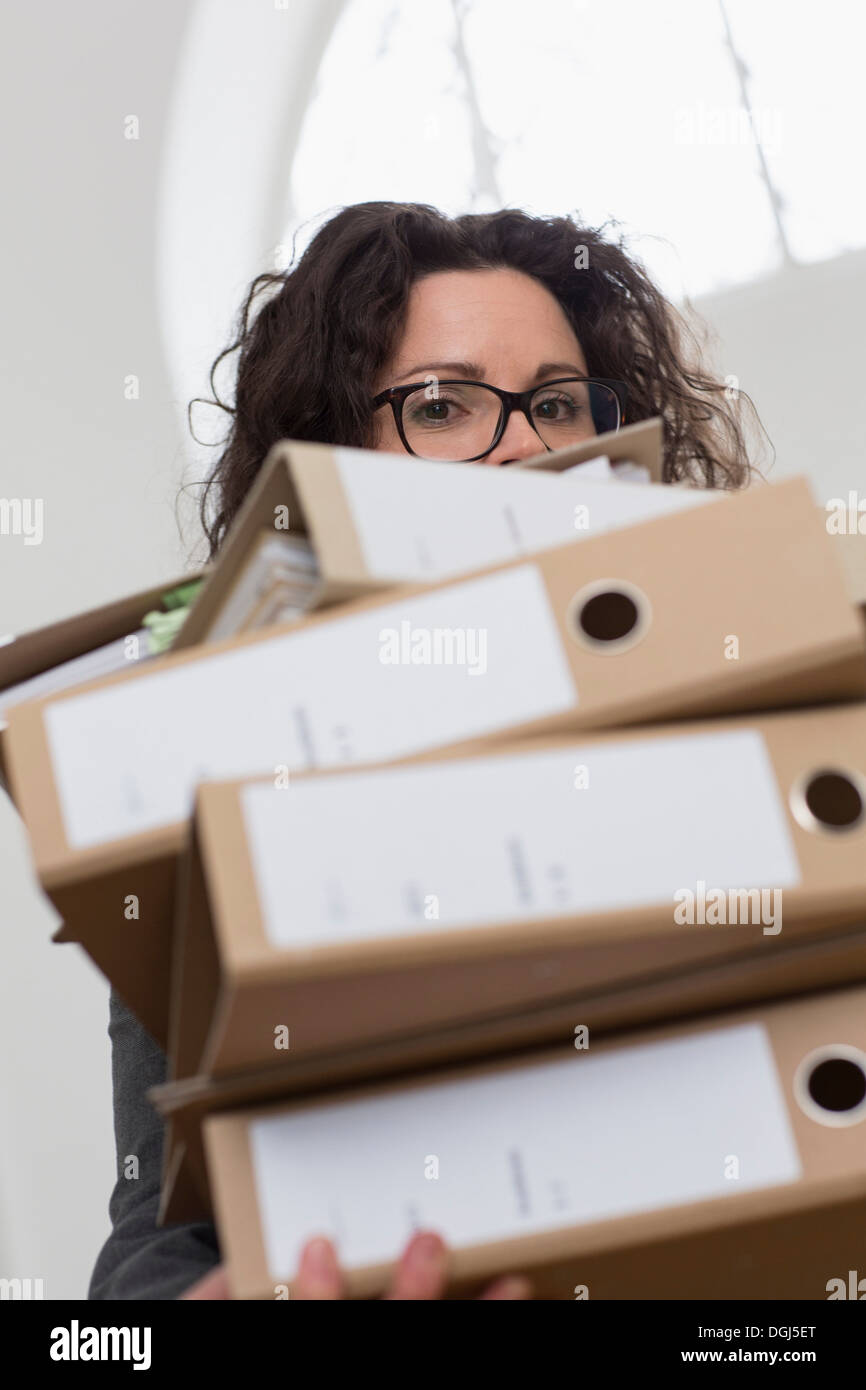 Businesswoman obscured by pile of folders - Stock Image