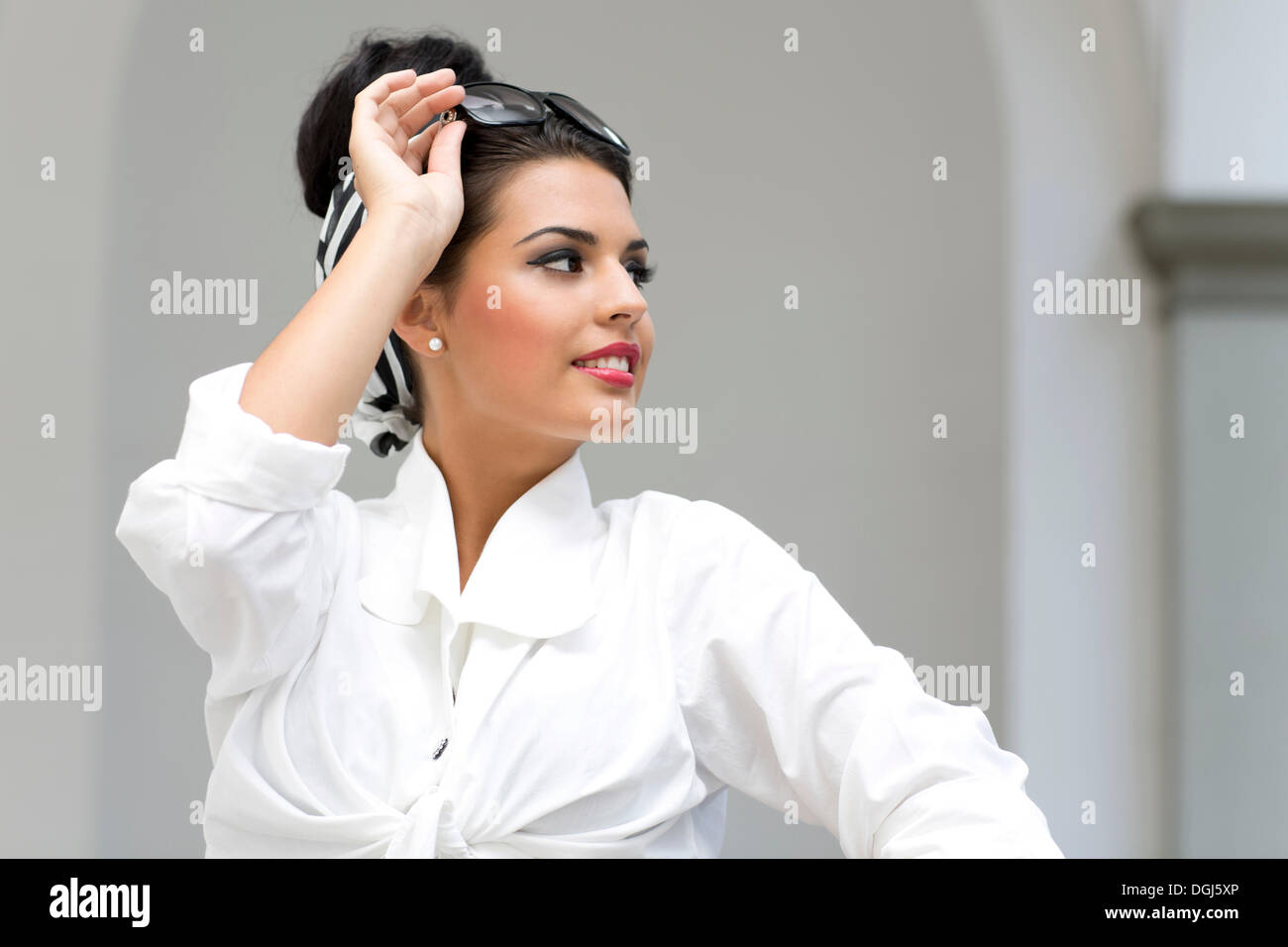 91b6a3206 Young woman with an updo hairstyle wearing sunglasses and a white shirt
