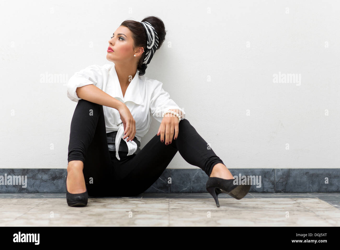 017262eb0 Young woman with an updo hairstyle wearing a white shirt, black leggings  and high heels posing while seated