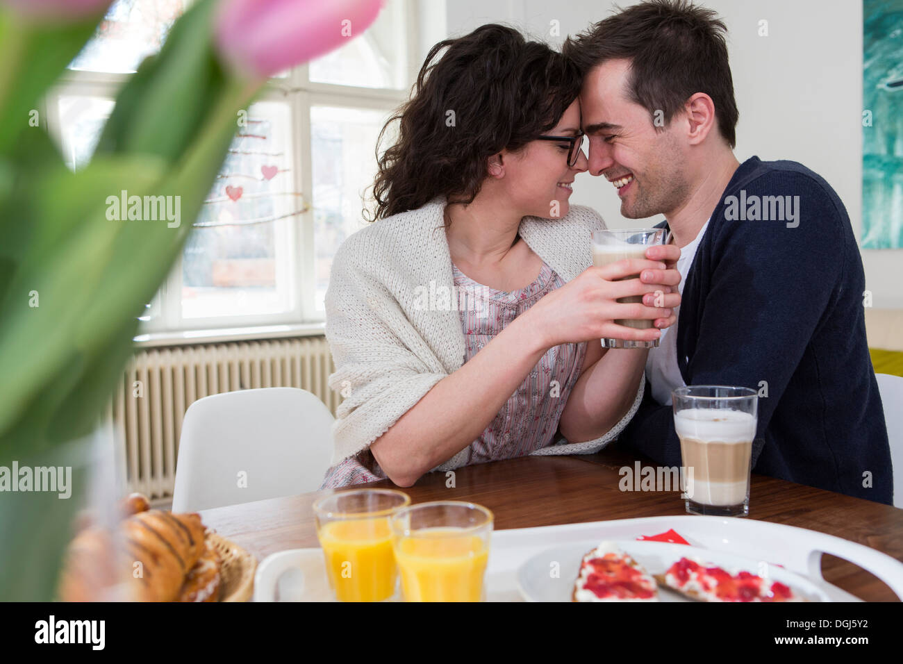 Heterosexual couple face to face at breakfast table - Stock Image