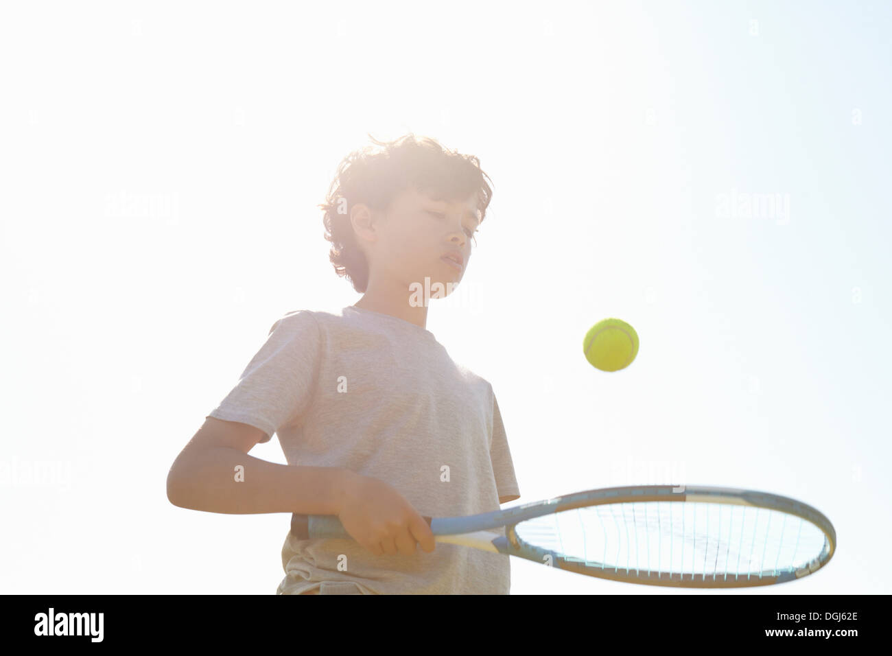 Boy bouncing ball on tennis racket - Stock Image