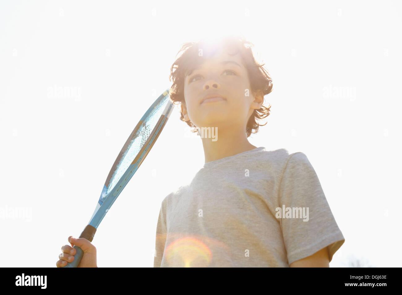 Boy holding up tennis racket - Stock Image