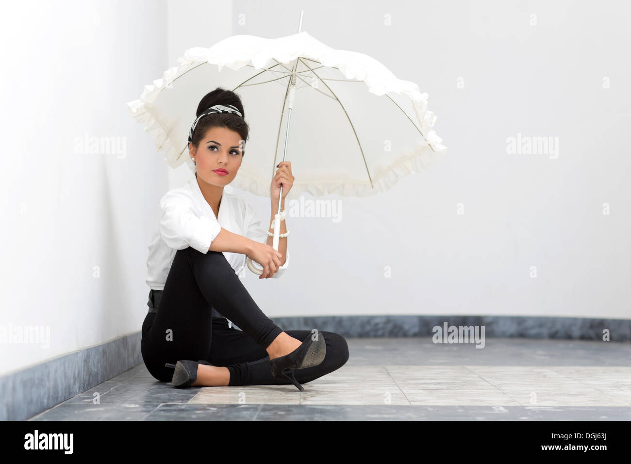 ff19cc63b Young woman with an updo hairstyle wearing a white shirt, black leggings  and high heels posing with a white umbrella while