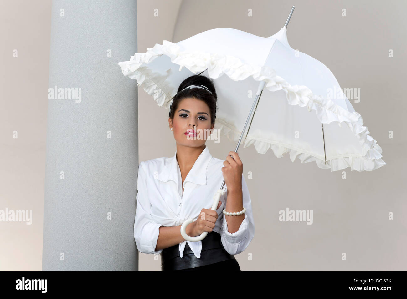 a01a9b7b7 Young woman with an updo hairstyle holding a white umbrella and wearing a white  shirt