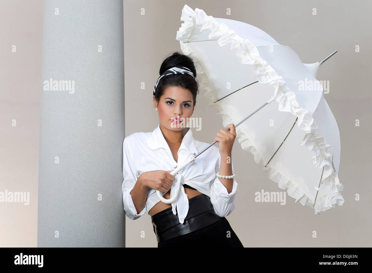 184bcc841 Young woman with an updo hairstyle wearing a white shirt and holding a white  umbrella