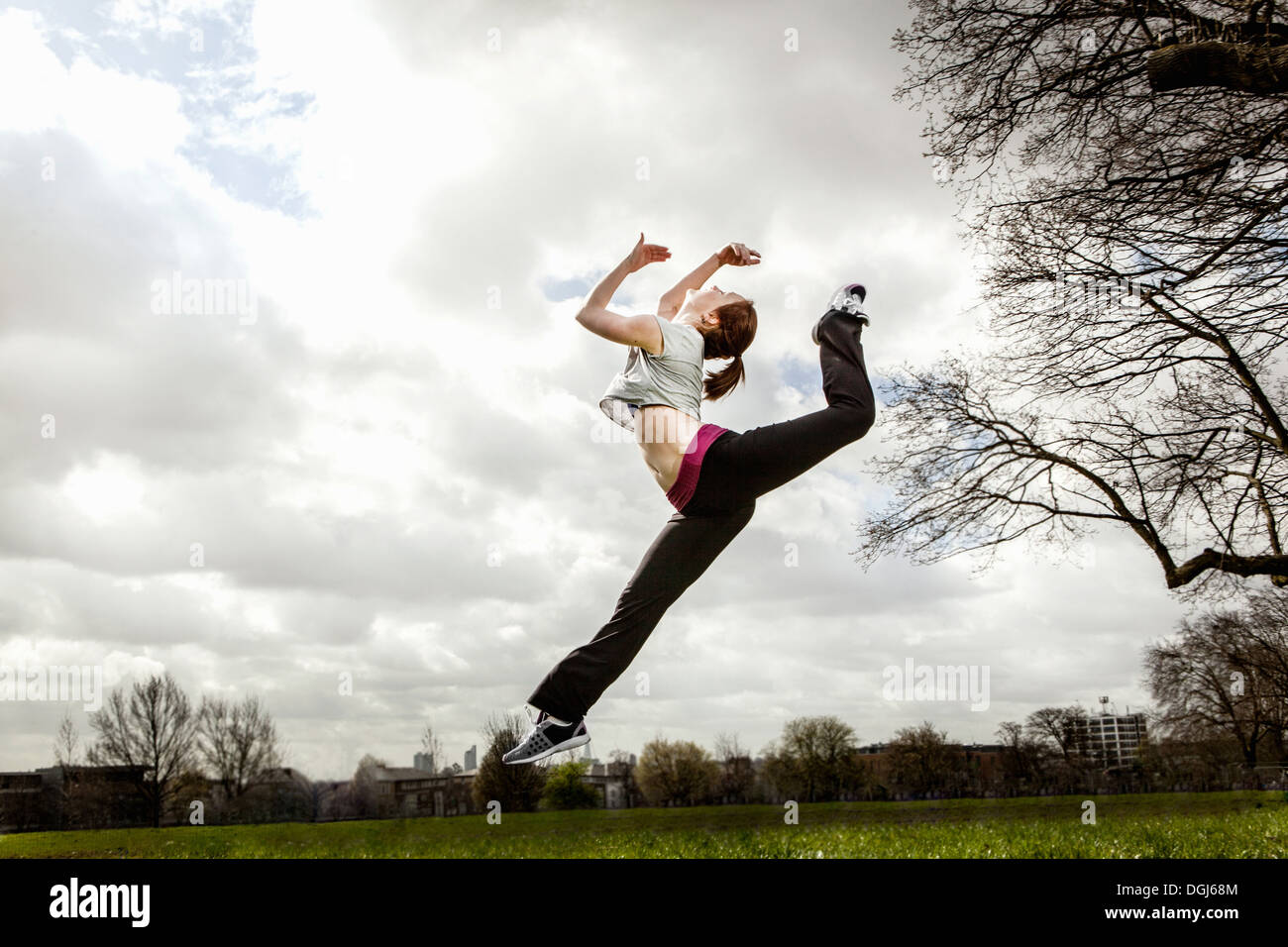 Woman jumping in mid air with bent leg - Stock Image