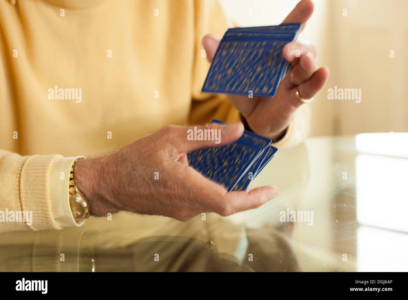 Close up of aged hands shuffling playing cards - Stock Image