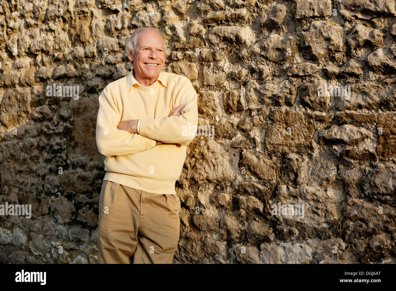 Senior man leaning against stone wall with arms crossed - Stock Image