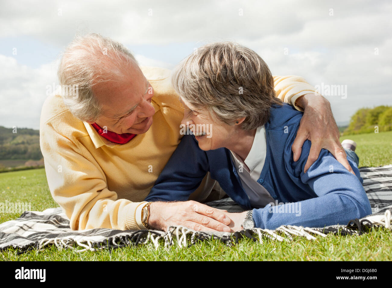 Husband and wife lying on stomach on blanket in field Stock Photo