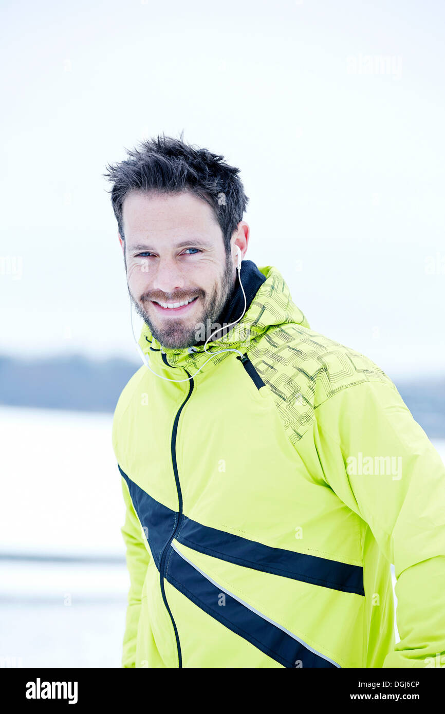 Man in yellow tracksuit smiling - Stock Image