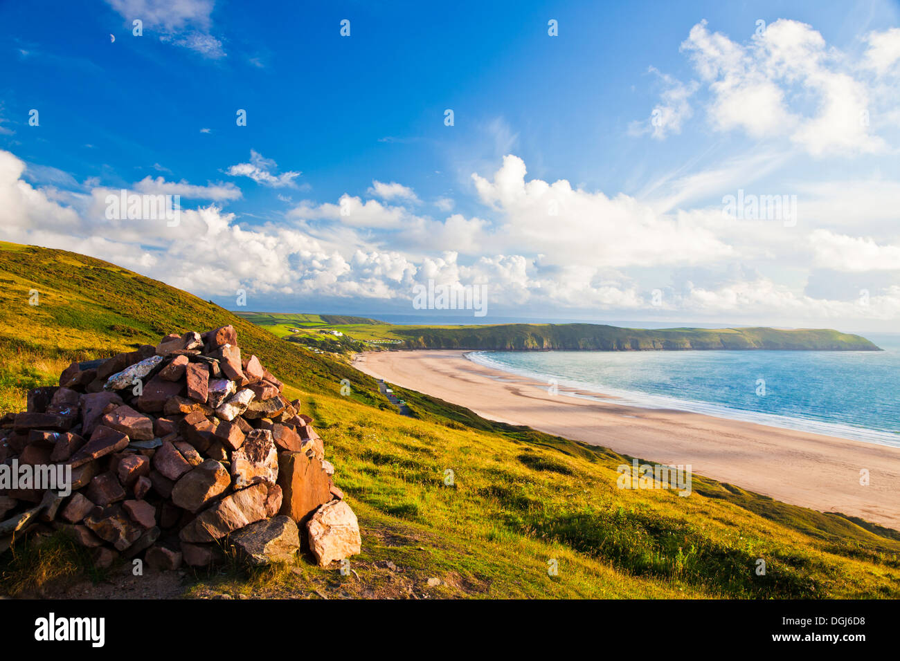 Evening light falls on the cairn on top of Potters Hill overlooking Putsborough Sands and Baggy Point. - Stock Image