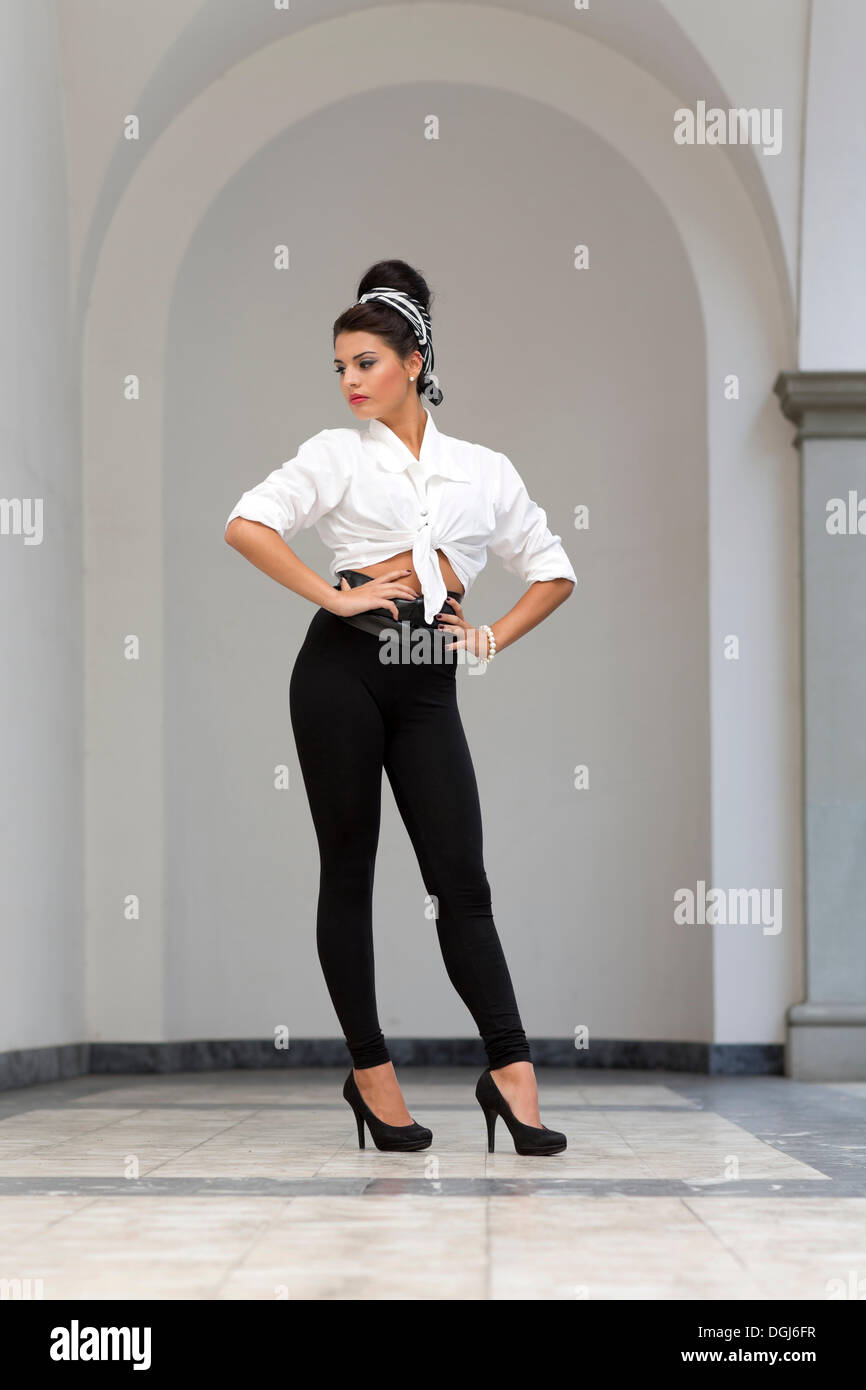 6a9df764d Young woman with an updo hairstyle, wearing a white shirt, black leggings  and high heels