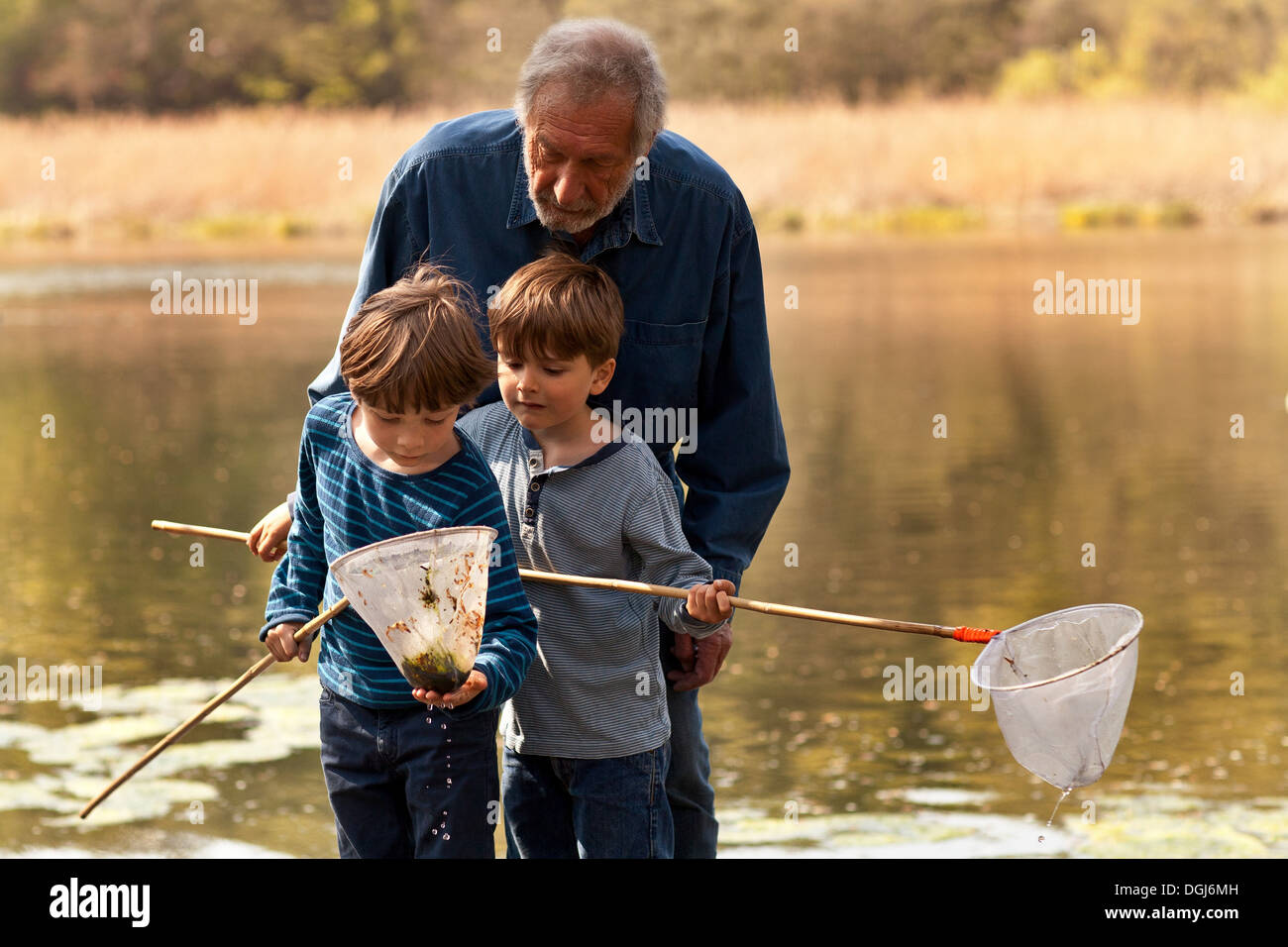 Grandfather and grandsons holding fishing nets by river - Stock Image