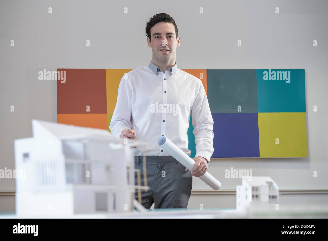 Architect holding plans in office with model buildings - Stock Image