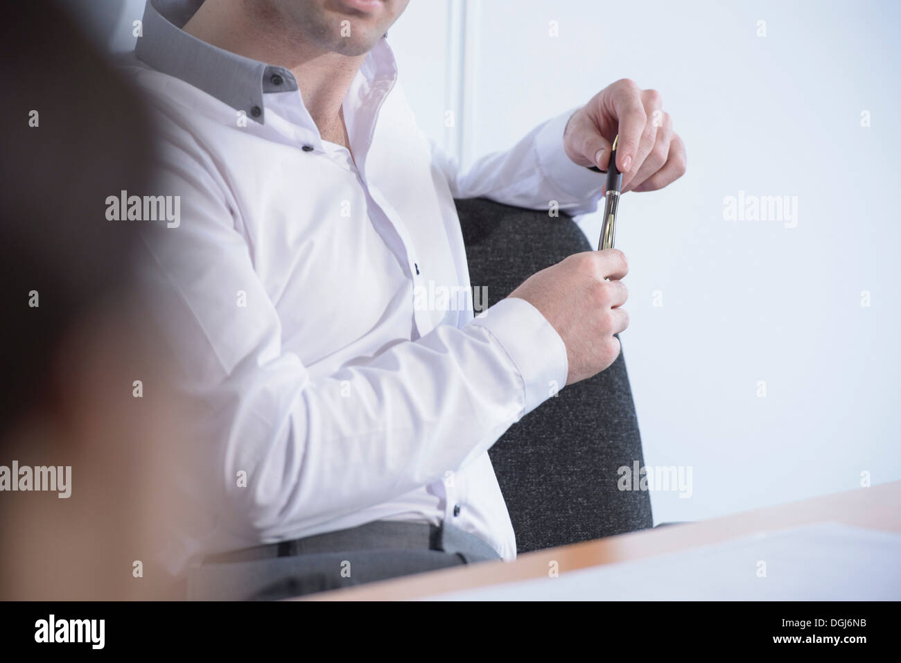 Man holding pen in business meeting, close up - Stock Image