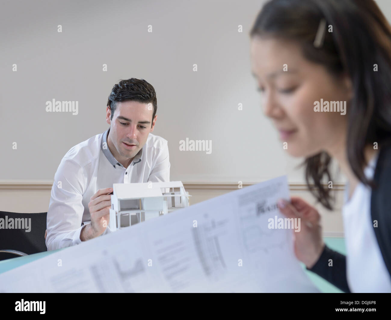 Architects inspecting model of building and plans in office - Stock Image