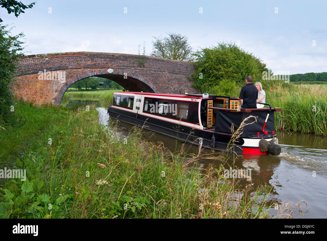 A couple enjoying a fine day on a narrowboat on the Ashby Canal. - Stock Image