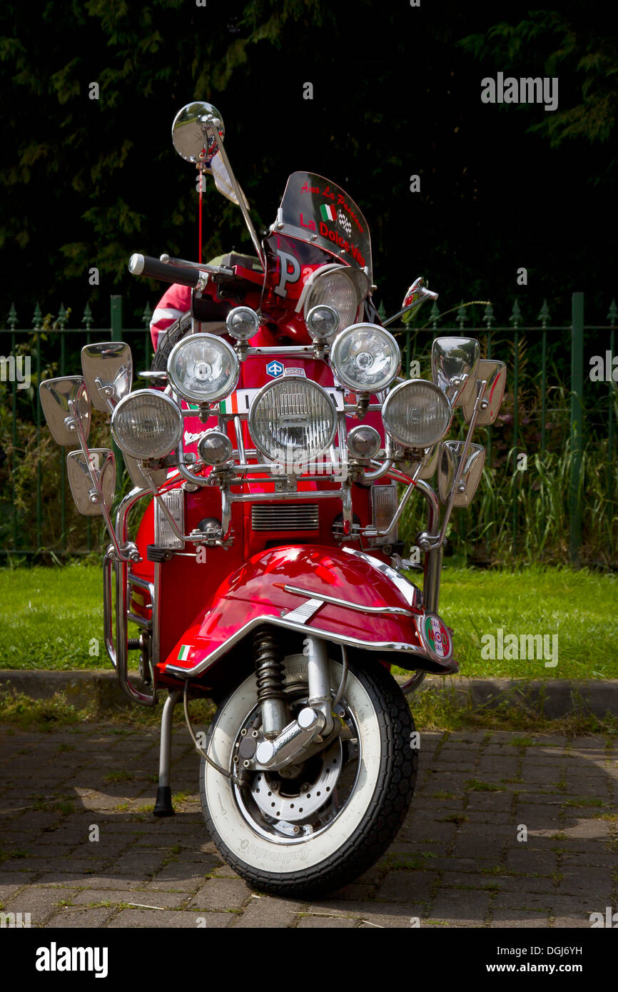 A red scooter with many lights and mirrors in the style of a mod scooter from the 1960's. - Stock Image