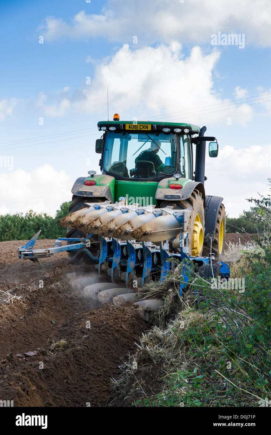 Ploughing with a modern John Deere tractor and reversible plough in North Norfolk. - Stock Image