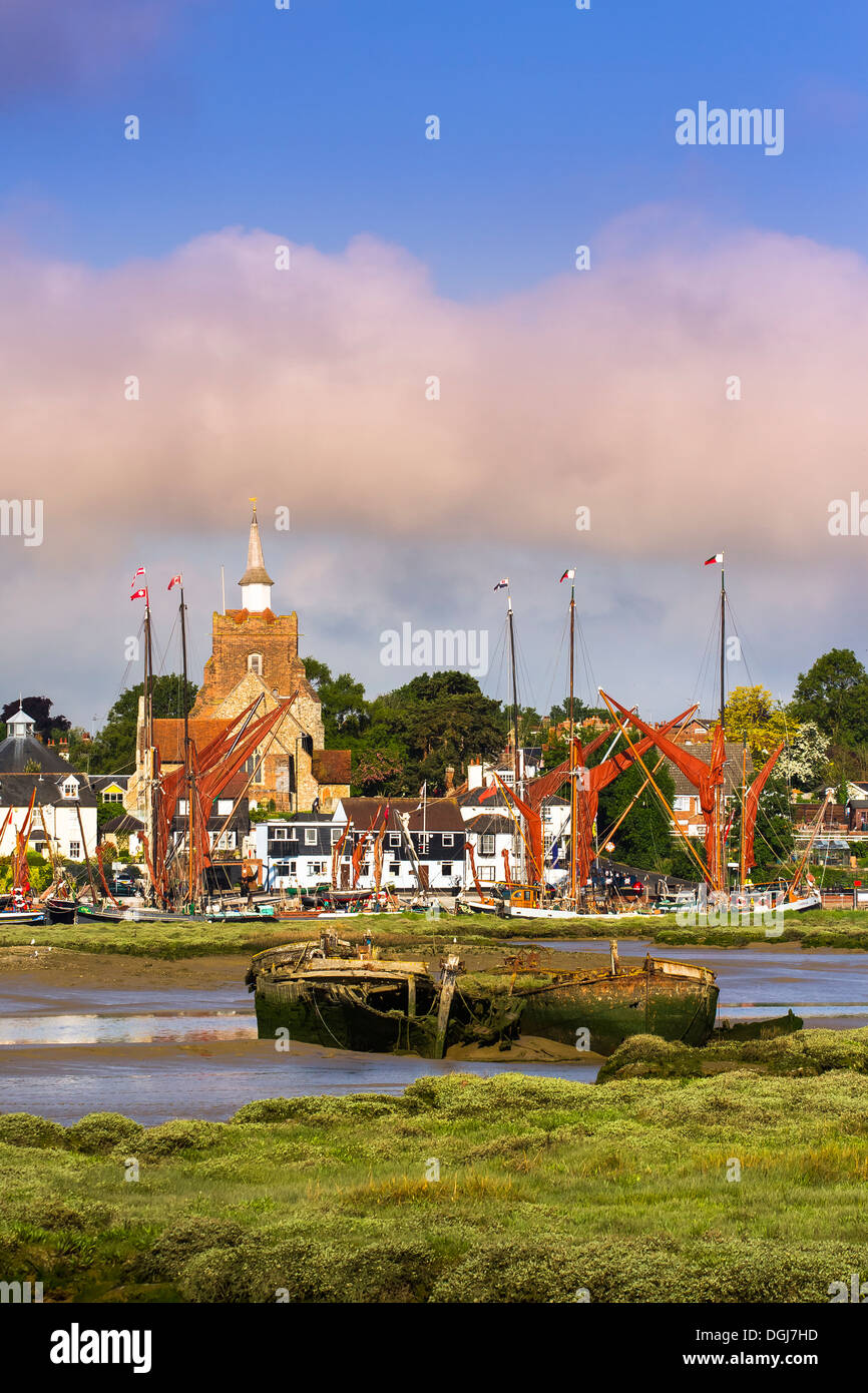 View of Maldon in Essex with several Thames sailing barges at the quay and the remains of two more in the mud of the estuary. - Stock Image