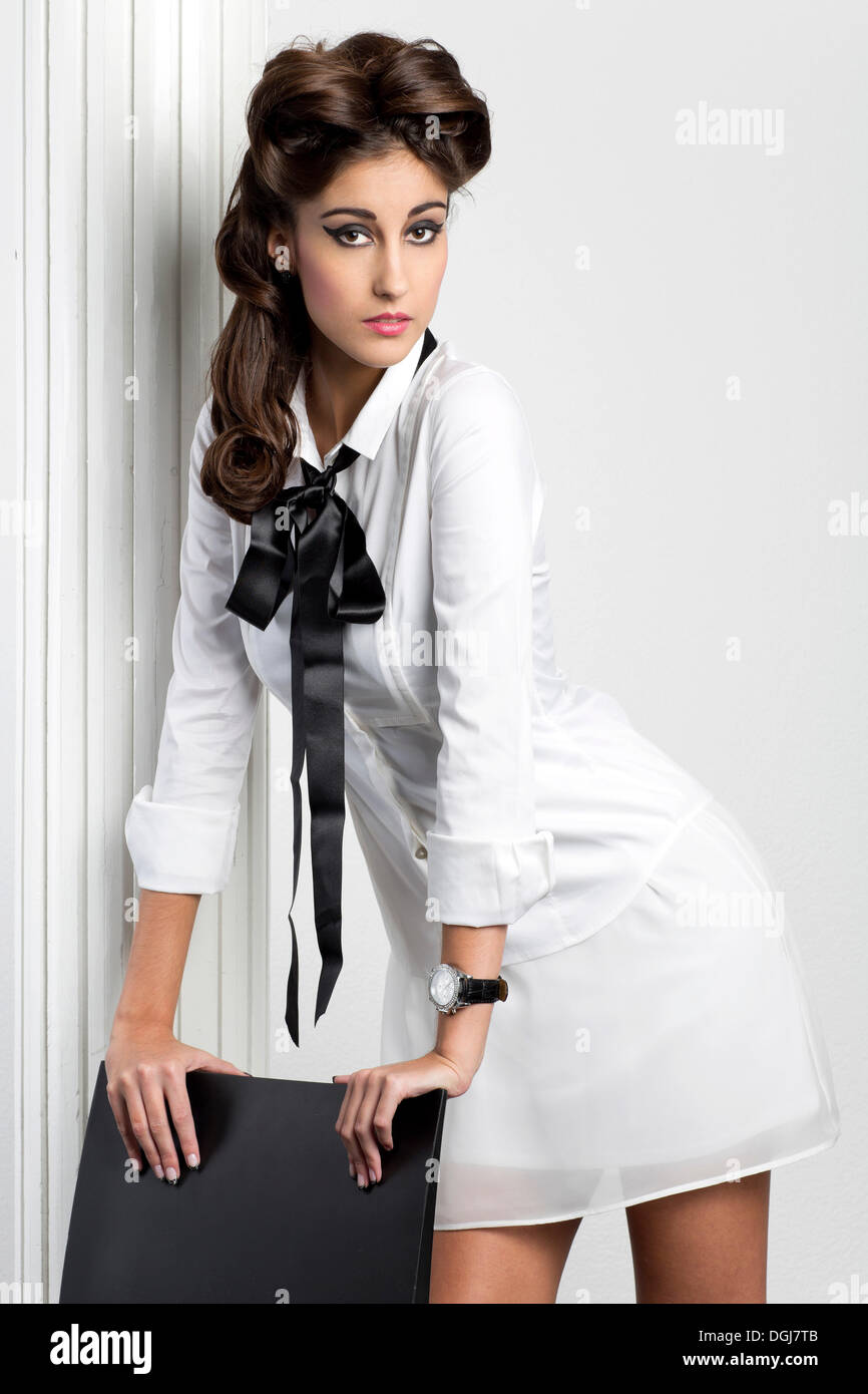 Young Woman With A White Blouse And Black Bow Posing In Front Of A
