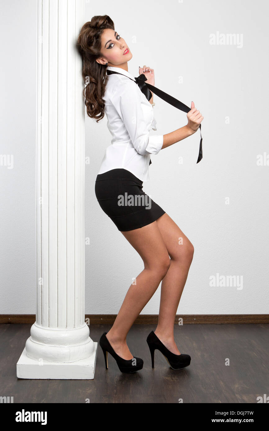 c29c6ba9c3 Young woman wearing a white blouse, a black skirt and high heels posing  against a