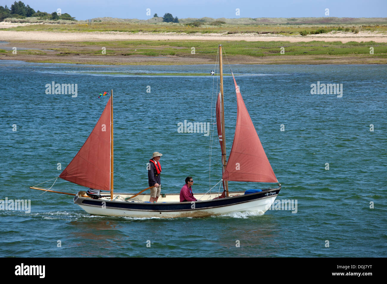 Two men sailing a boat down the channel between the harbour and beach at Wells Next The Sea. Stock Photo