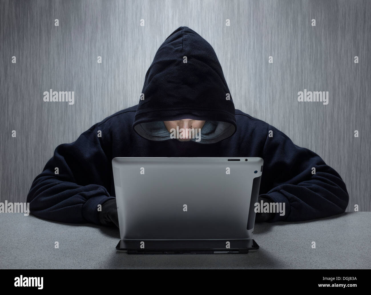 An anonymous hooded male using a tablet computer to represent a cyber criminal. - Stock Image