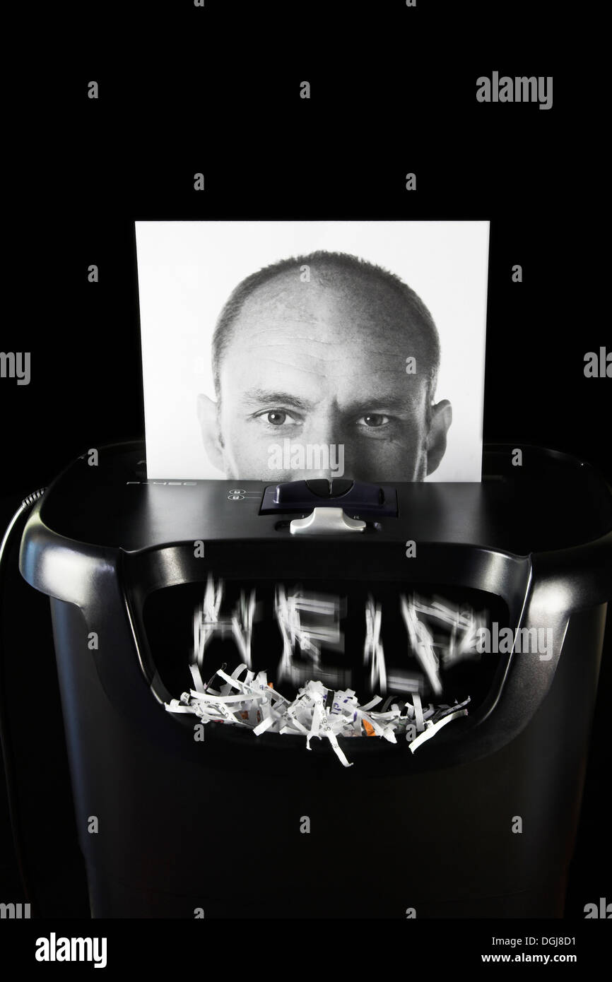 Photograph of a man's face being put through a paper shredder. - Stock Image
