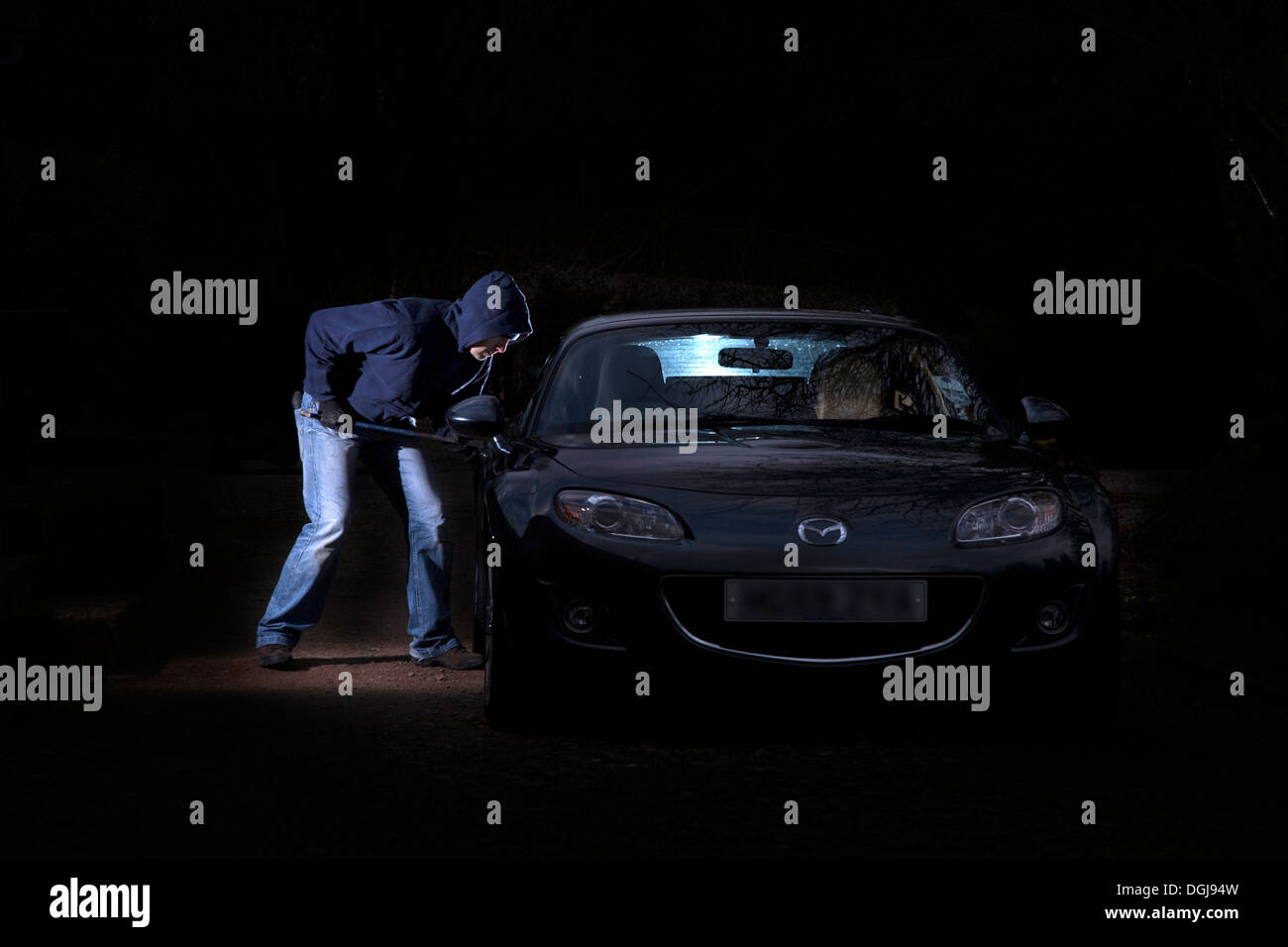 A man breaking into a parked car at night. - Stock Image