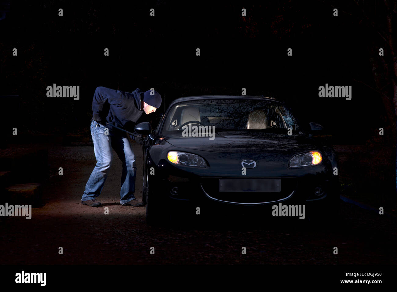 A man breaking into a parked car at night. Stock Photo