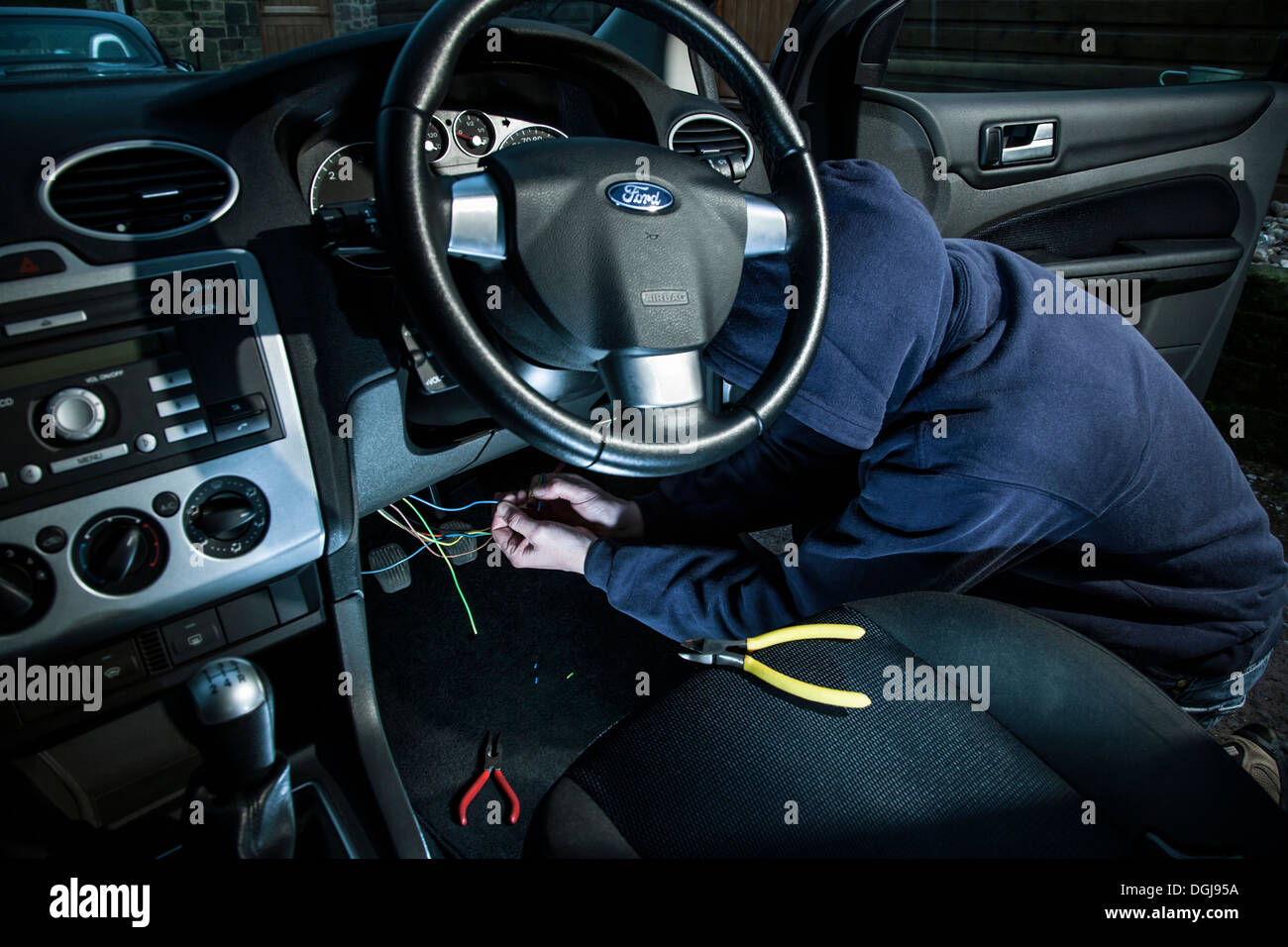 A man wearing a hoody hot wiring a car. - Stock Image