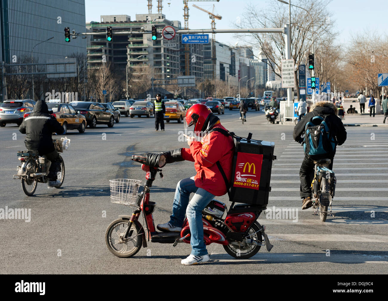 Motorised McDonalds delivery seeking the delivery address on a smartphone at a crossroads, Beijing, China, Asia - Stock Image