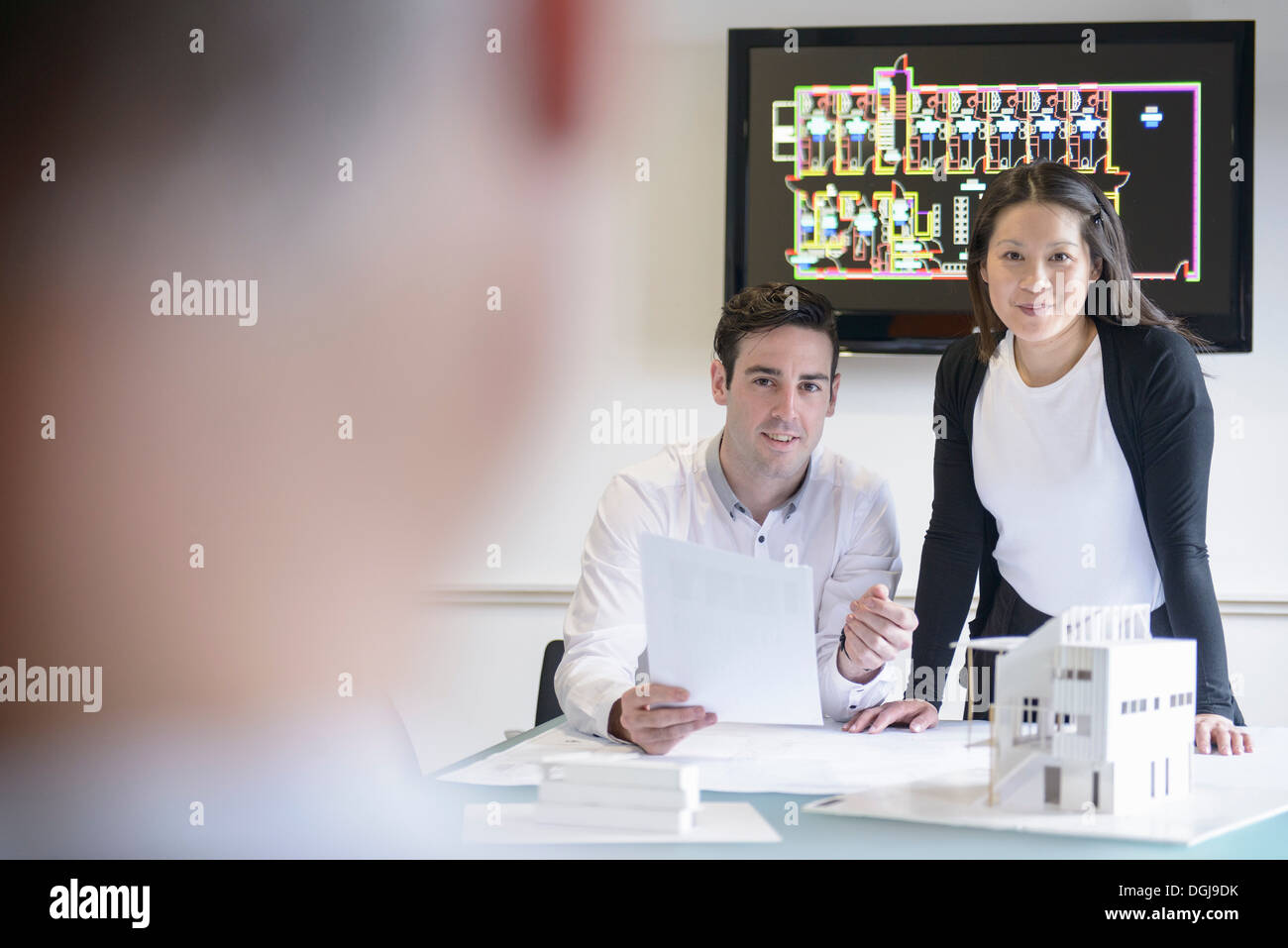 Architects making presentation in boardroom with model building - Stock Image