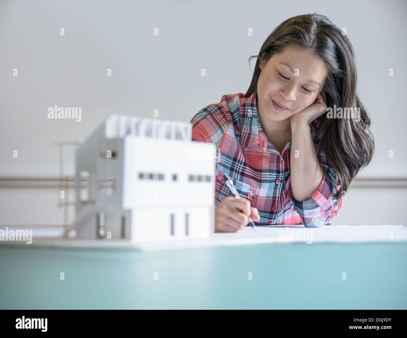 Architect working next to model building - Stock Image