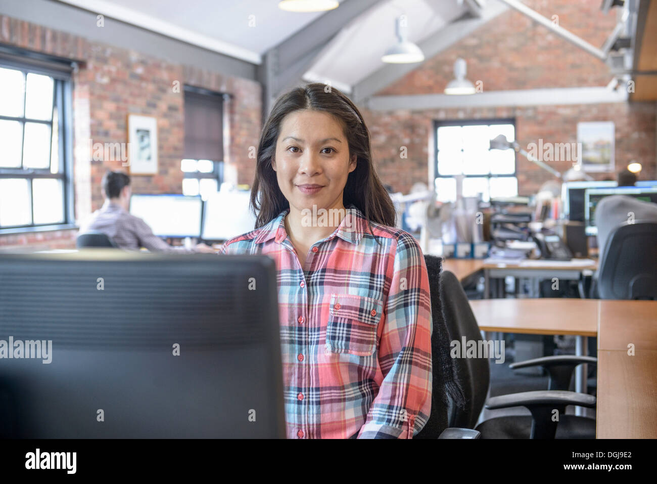 Office worker at desk, portrait - Stock Image