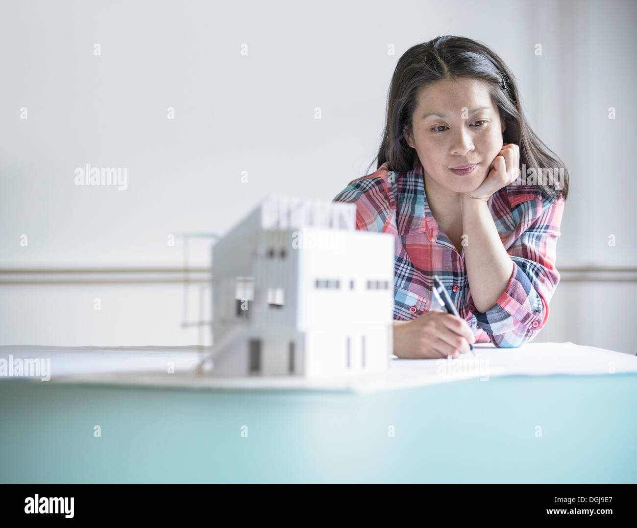 Architect working next to model building Stock Photo